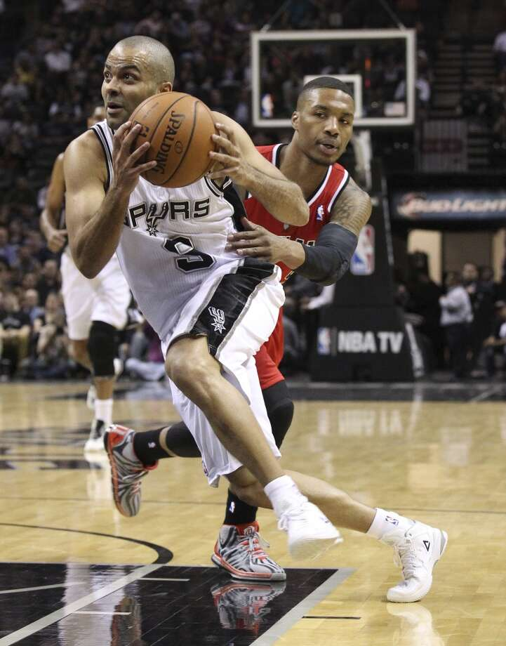 Spurs' Tony Parker (09) gets a step on Portland Trailblazers' Damian Lillard (00) in the first half at the AT&T Center on Wednesday, March 12, 2014. Photo: Kin Man Hui, San Antonio Express-News