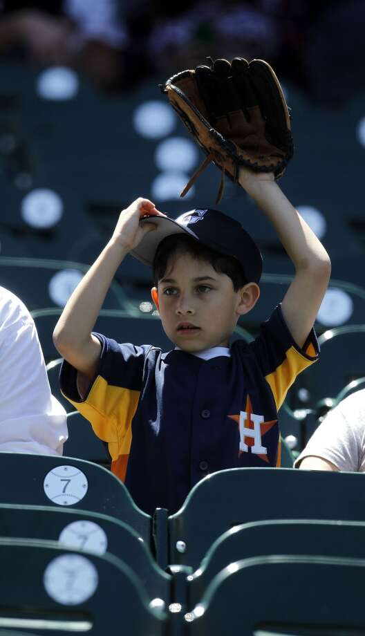 Max Deleon, 7, of Katy, sits in his seats with his dad, Ramiro, before the start of the game. Photo: Karen Warren, Houston Chronicle