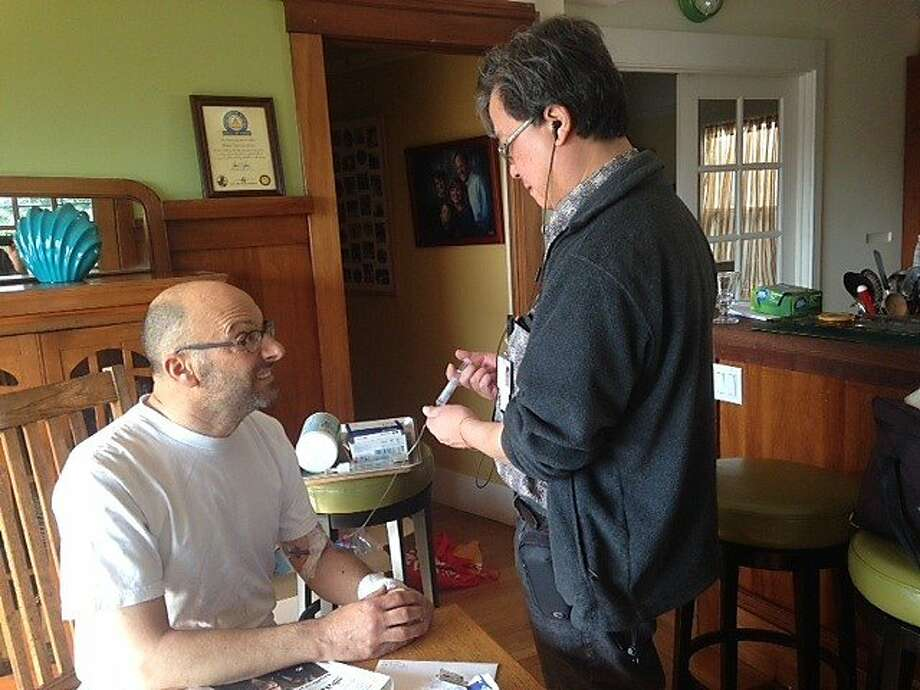 Reporter Mike Sugerman, who has recovered well enough from a heart condition to return to KPIX and KCBS, gets an injection at home from nurse Dennis Huey. Photo: Janice Wright