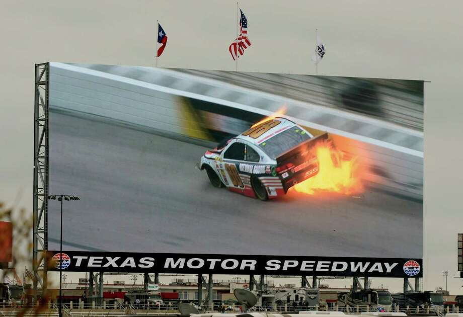 A video screen shows a replay of Dale Earnhardt Jr.'s (88) car during a wreck at the NASCAR Sprint Cup series auto race at Texas Motor Speedway, Monday, April 7, 2014, in Fort Worth, Texas. Photo: Larry Papke, AP / FR58581 AP