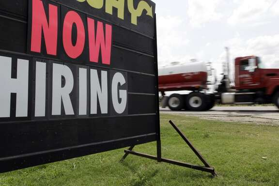 """An oil truck passes a """"now hiring"""" sign, Wednesday, May 9, 2012, in Kenedy, Texas. A UTSA report says South Texas's Eagle Ford Shale supported nearly 48,000 jobs last year while creating overnight boom towns cashing in on a $25 billion economic windfall. The energy rush that started in 2008 mushroomed into nearly 1,700 wells last year. (AP Photo/Eric Gay)"""