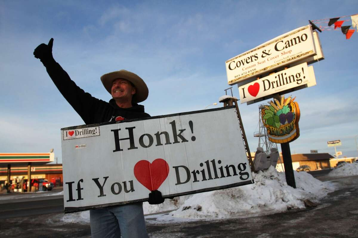 This Jan. 16, 2014 photo, George Burnett, owner of Covers & Camo in Vernal, Utah holds up a sign outside his business. The Uinta Basin oil boom has made Duchesne County the nation's second fastest-growing (for counties with at least 10,000 people), and Vernal the nation's sixth fastest-growing