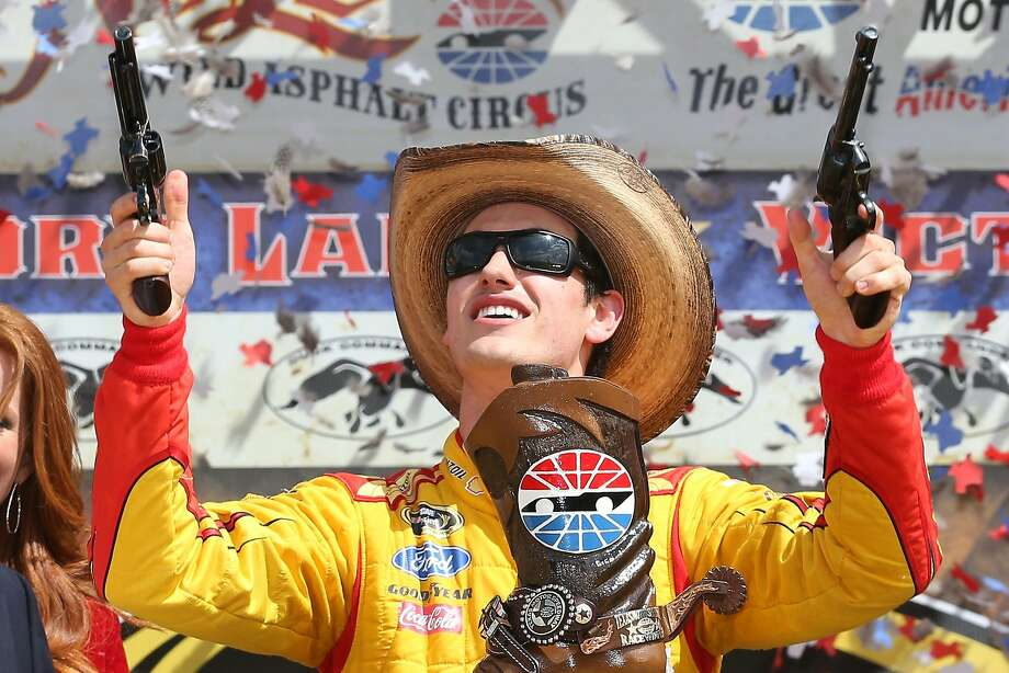 Joey Logano celebrates in Victory Lane after winning the NASCAR Sprint Cup Series Duck Commander 500 at Texas Motor Speedway in Fort Worth. Photo: Chris Graythen, (Credit Too Long, See Caption)
