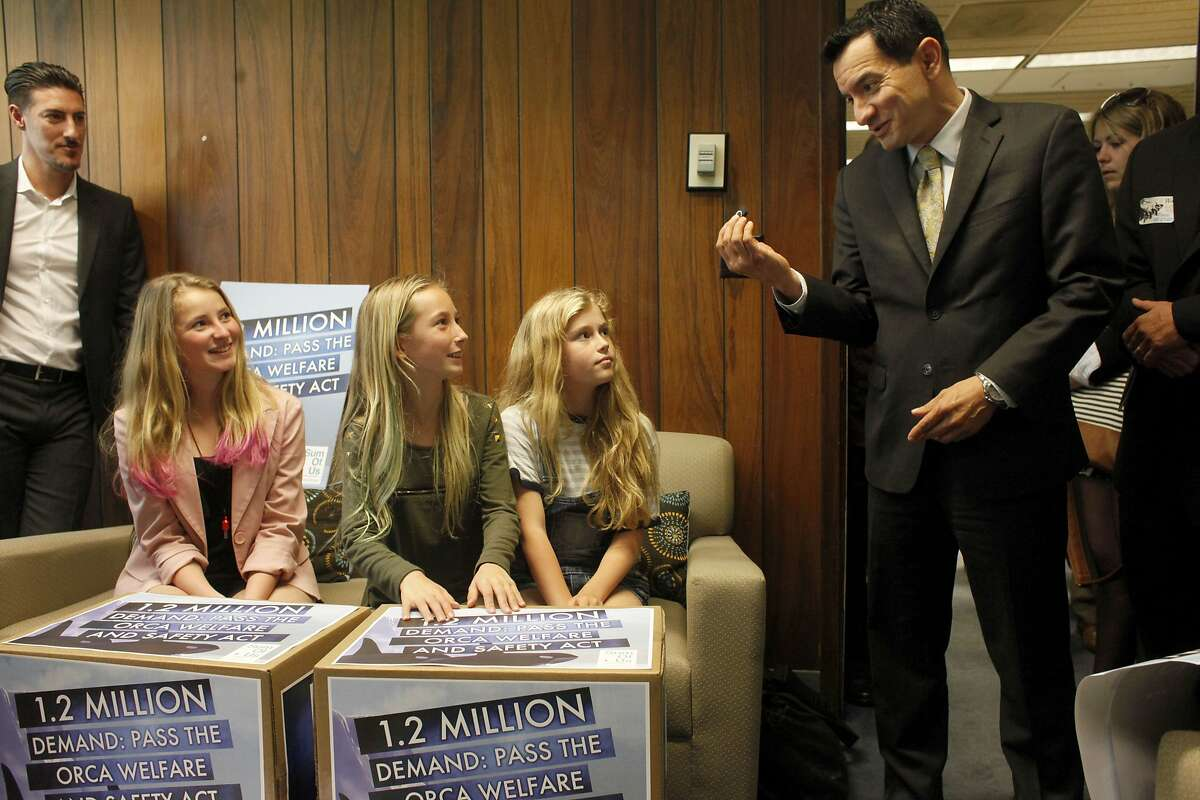 Ava Kotler, left , sister Kirra Kotler and Lizzie Gordon deliver 1.2 million signature to 63rd District Assemble member Anthony Rendon in support of AB 2140 bill, Monday April 7, 2014, in Sacramento, Calif. The bill will ensure the welfare of captive orcas and the safety of their trainers in the state of California.