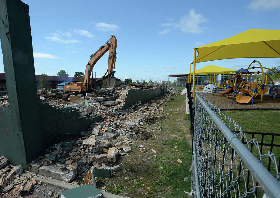 Workers demolish the remains of the Oil City Brass Works building on Monday. The structure was hoped to be used as a children's museum, but extensive damage prevented renovations.  Photo taken Monday, April 07, 2014 Guiseppe Barranco/@spotnewsshooter Photo: Guiseppe Barranco, Photo Editor