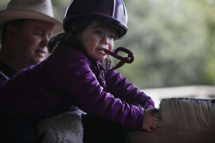 Grace Wilsey, who has a rare genetic disease, uses a chew tool to exercise her oral motor muscles at an equine therapy session in Woodside.