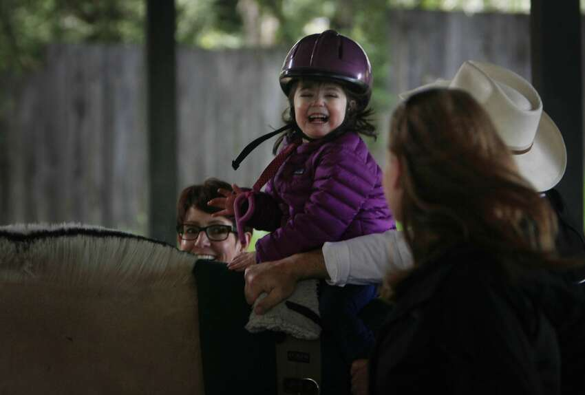 Grace trots on a therapy horse with help from a therapist and volunteers at the equine center.