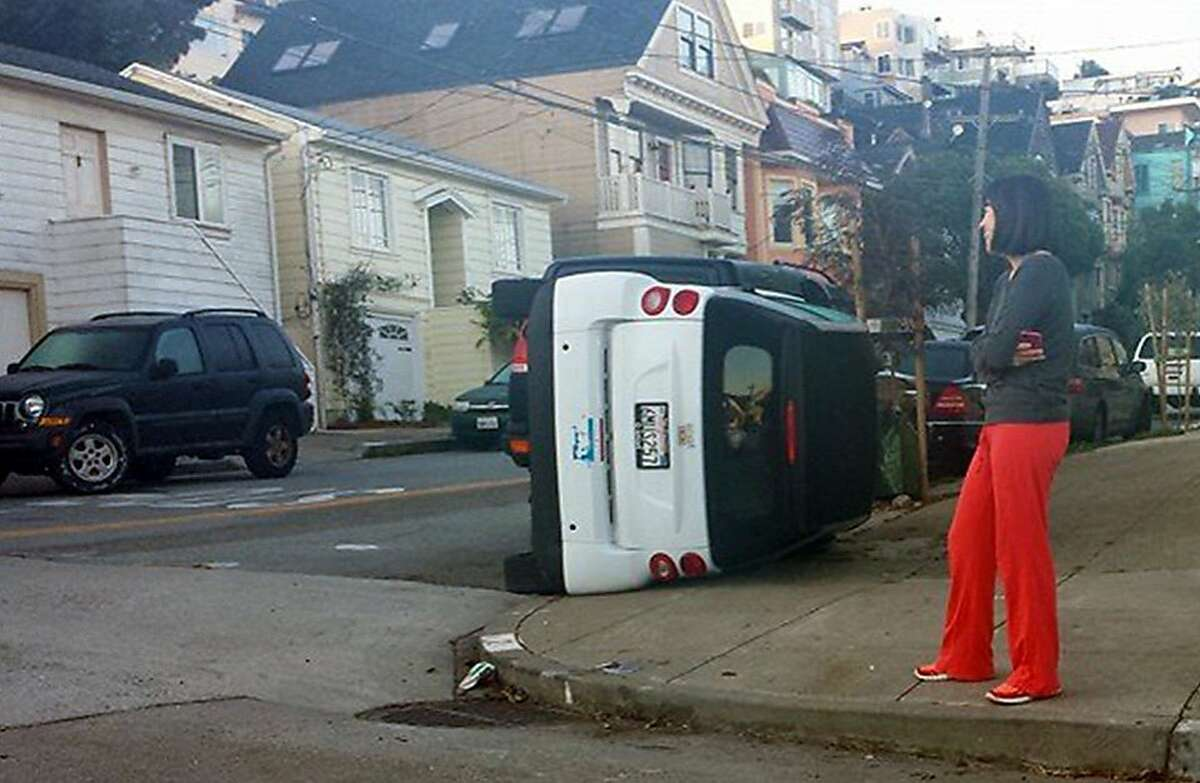 An unidentified woman looks at an upended Smart Car at 120 Coso Avenue in San Francisco.