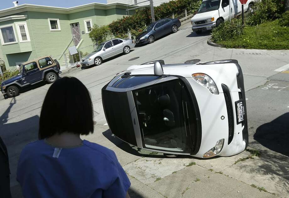 Shelley Gallivan looks at her friend's Smart car that was tipped over at Prospect and Coso avenues. Photo: Jeff Chiu, Associated Press