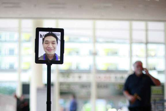 Jay Liew of Double Robotics is seen on an iPad as he demonstrates Double, an office robot that looks something like a Segway with an iPad attached.