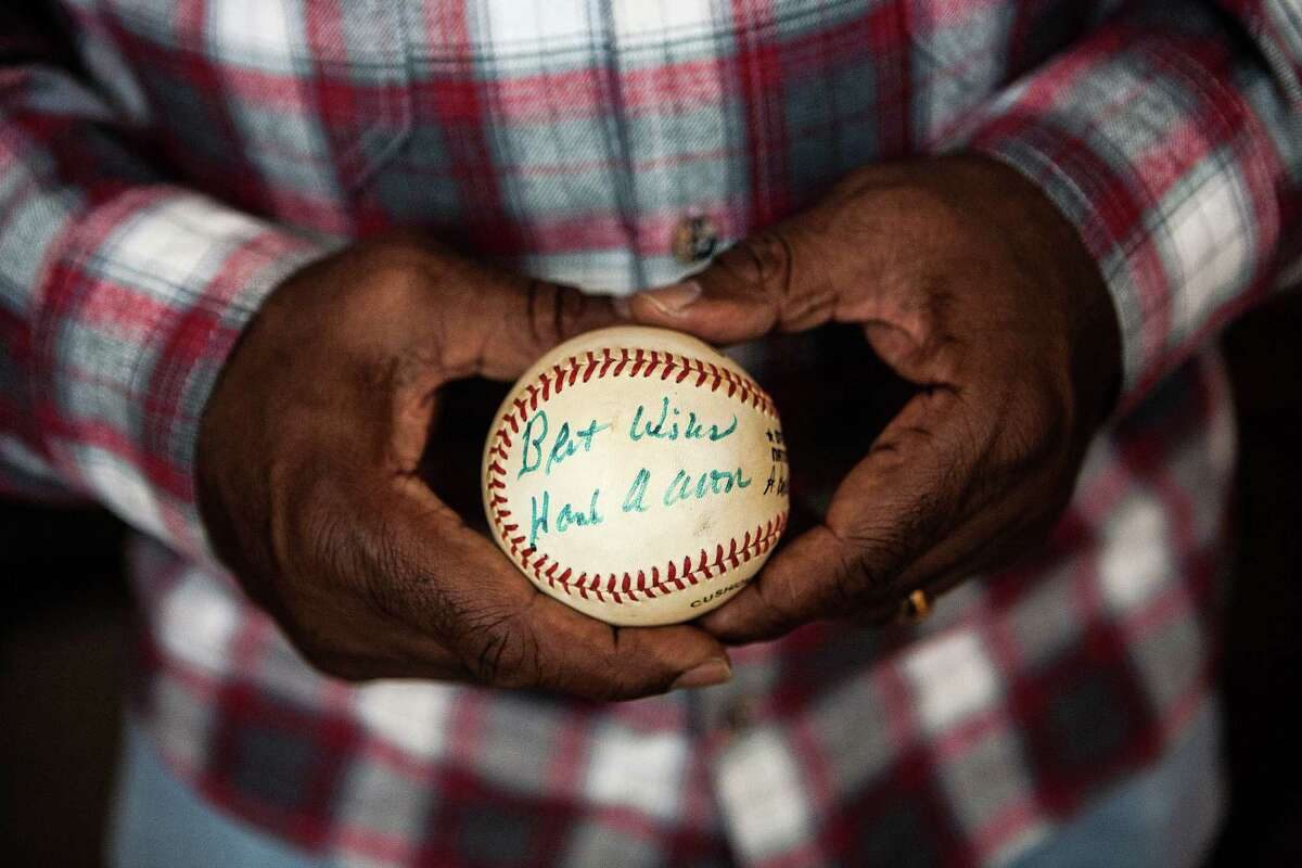 Garr holds a baseball autographed by Aaron, who took the younger player under his wing during their days in Atlanta.