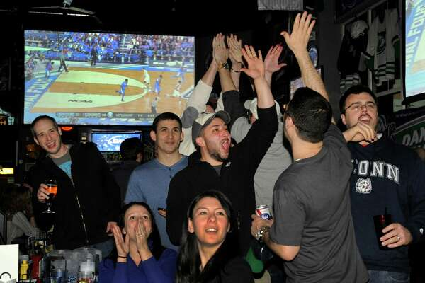 University of Connecticut basketball fans cheer for their team at the 1st and 10 Sports Bar & Grill in New Milford, Conn. where patrons watched the mens national championship game against Kentucky Monday night, April 7, 2014.