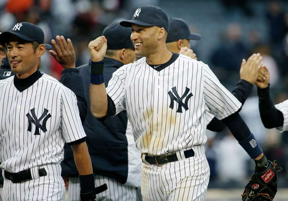New York Yankees right fielder Ichiro Suzuki, left, and shortstop Derek Jeter celebrate the Yankees 4-2 victory over the Baltimore Orioles in the Yankees home  MLB American League baseball opener against the Baltimore Orioles, at Yankee Stadium in New York, Monday, April 7, 2014.  The Yankees defeated the Orioles 4-2. (AP Photo/Kathy Willens) ORG XMIT: NYY124 Photo: Kathy Willens / AP