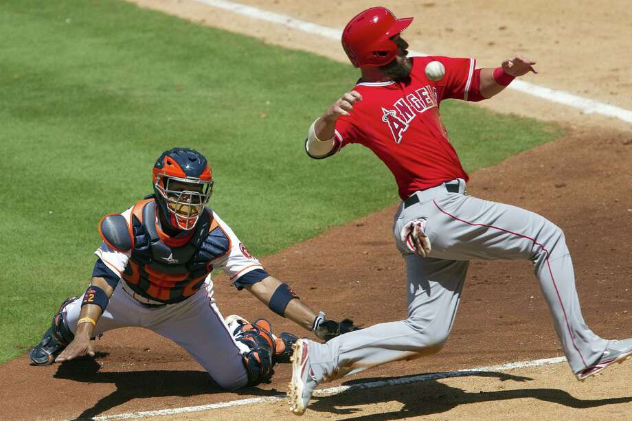 Astros catcher Carlos Corporan misses a catch that allows the Angels' Ian Stewart to score in the sixth. Photo: Jason Fochtman / Associated Press / Conroe Courier