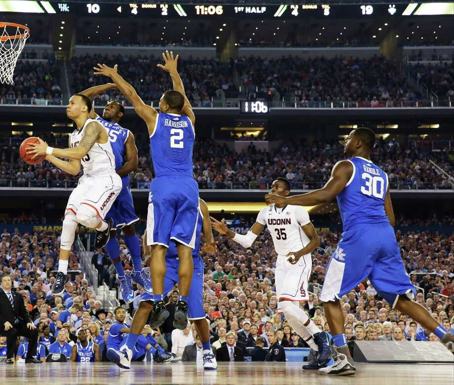 Connecticut guard Shabazz Napier shoots between Kentucky guard Dominique Hawkins (25) and guard Aaron Harrison (2) during the first half of the NCAA Final Four tournament college basketball championship game Monday, April 7, 2014, in Arlington, Texas. (AP Photo/David J. Phillip)  ORG XMIT: FF131 Photo: David J. Phillip / AP