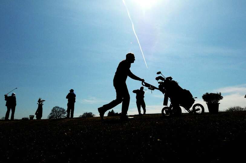 Golfers practice on the drving range as other golfers head to the first tee at the Capital Hills at