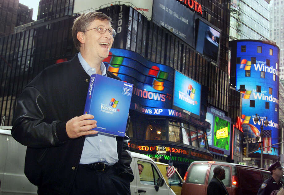 FILE - In this Oct. 25, 2001 file photo, Microsoft chairman Bill Gates stands in New York's Times Square to promote the new Windows XP operating system. On Tuesday, April 8, 2014, Microsoft will end support for its still popular Windows XP. With an estimated 30 percent of businesses and consumers still using the 12-year-old operating system, the move could put everything from the data of major financial institutions to the identities of everyday people in danger if they don't find a way to upgrade soon. (AP Photo/Richard Drew, File) ORG XMIT: NY205 Photo: Richard Drew / AP