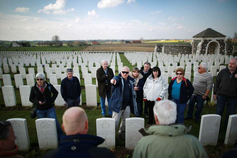 Tour Guide Vik Piuk (5L) informs visitors at Tyne Cot cemetery near Passchendaele, Belgium. Tyne Cot is the largest Commonwealth war cemetery in the world. There are 11,956 Commonwealth servicemen of the First World War buried or commemorated here. A number of events will be held this year to commemorate the centenary of the start of World War One Photo: Peter Macdiarmid, Getty Images