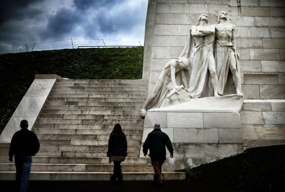 Visitors walk past the 'Breaking the Swords' sculpture at the Canadian National Vimy Memorial in Vimy, France. A number of events will be held this year to commemorate the centenary of the start of World War One. Photo: Peter Macdiarmid, Getty Images / 2014 Getty Images