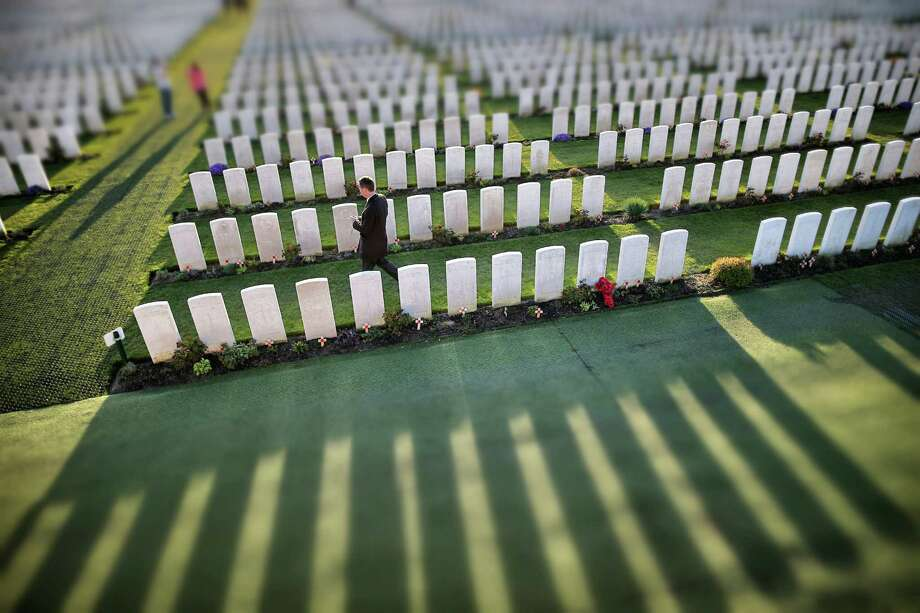 Visitors walk amongst rows of headstones at Tyne Cot Commonwealth War Graves Commission cemetery on March 24, 2014 in Passchendaele, Belgium. Tyne Cot is the largest Commonwealth war cemetery in the world. There are 11,956 Commonwealth servicemen of the First World War buried or commemorated here. Photo: Peter Macdiarmid, Getty Images / 2014 Getty Images