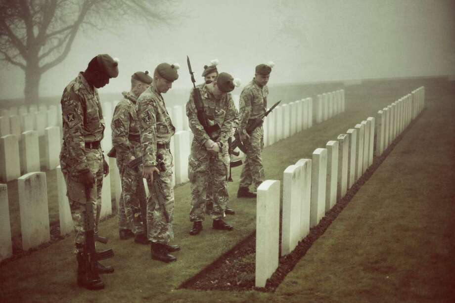 Soldiers of The 2nd Battalion The Royal Regiment of Scotland look at headstones as they rehearse for a re-burial ceremony in Loos British Cemetery in Loos-en-Gohelle, France. Almost 100 years after they were killed in action in the World War One battle of Loos in 1915, twenty British soldiers will be re-interred in the Commonwealth War Graves Commission Loos British Cemetery in Northern France. Private William McAleer, from the 7th Battalion the Royal Scottish Fusiliers, was found with his identity disc, but others found him remain unidetified and will be buried as soldiers 'Known unto God'.  However, among the other soldiers are a Northumberland Fusilier, a further six Royal Scottish Fusiliers, a member of the York and Lancaster Regiment, two Queens Own Cameron Highlanders and nine others for whom no regiment has been identified. Photo: Peter Macdiarmid, Getty Images / 2014 Getty Images