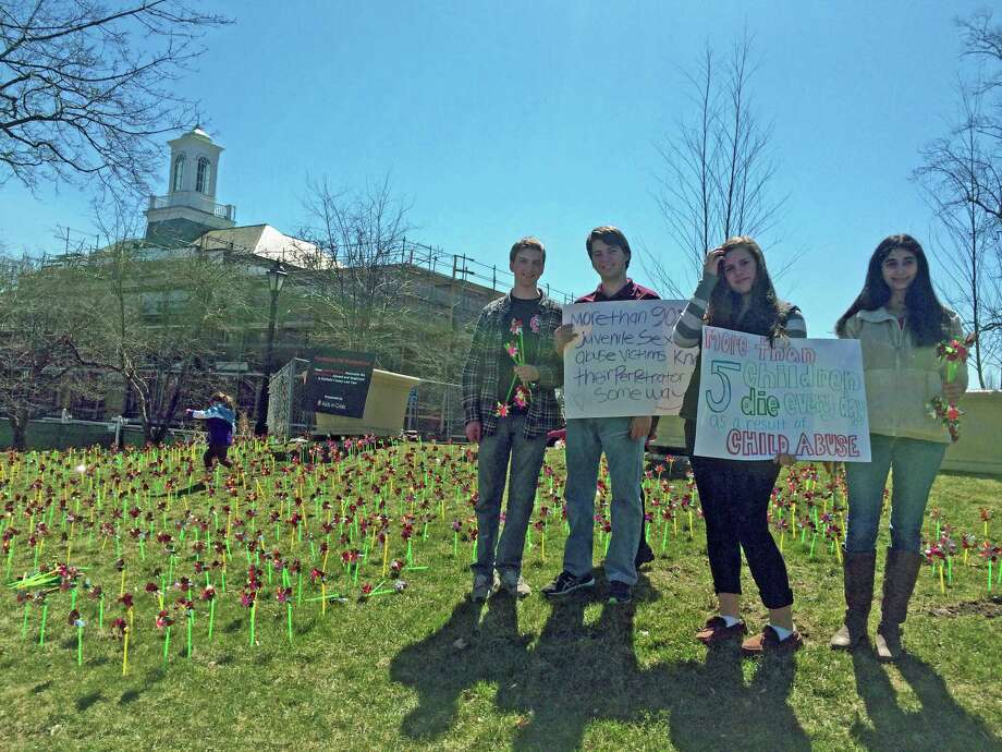Students from New Canaan High School placed 1,864 pinwheels on the lawn of Vine Cottage Sunday, April 6. The symbols of childhood commemorate the 1,864 children abused and neglected in Fairfield County last year. New Canaan High School TeenTalk counselor Ed Milton led the effort; TeenTalk is a safe, confidential outlet for students struggling with difficult circumstances and as part of the wider network of Kids in Crisis, enables students to build coping skills and, when necessary, find safe havens. From left are, Jason Kurtzman, Kevin Kurtzman, Kaylee Paladino and Marissa Tamburro. Photo: Contributed Photo, Contributed / New Canaan News Contributed