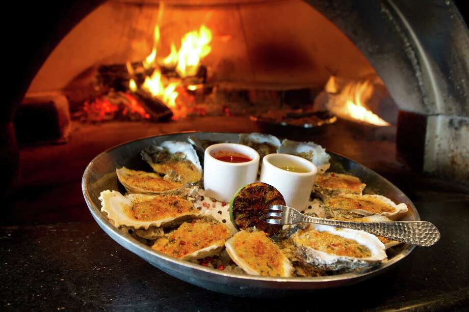 Caracol's Ostiones Asados, wood-roasted Gulf oysters with chipotle butter, seems destined to become one of Houston's definitive dishes. Photo: Brett Coomer, Staff / © 2014 Houston Chronicle
