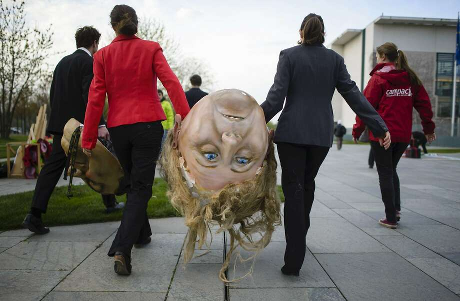 "Bring me the head of Angela Merkel: BUND and Campact environmental activists tote the German leader's ""head""  before a demonstration against the reform of the Renewable Energy Sources Act in Berlin. Berlin is implementing a deep reform of its system of subsidies for clean energy. Photo: Clemens Bilan, AFP/Getty Images"