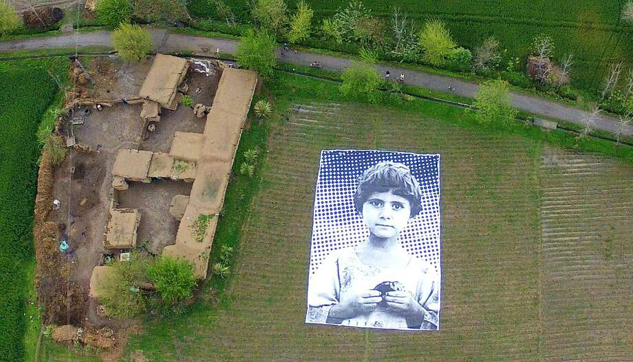Orphaned by a drone: At an undisclosed location in Pakistan's northwestern Khyber-Pakhtunkhwa province, artists installed a poster bearing the image of a Pakistani girl whose parents, lawyers say, were killed in a drone strike. The goal of the project is to generate empathy among U.S. drone operators by placing giant posters of children in the country's troubled tribal regions. Photo: Inside Out Project, AFP/Getty Images