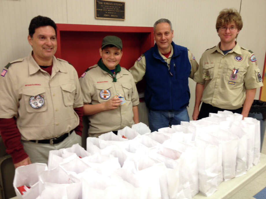 Reuben Keating, JonCarlo Keating, Patrick Gentile and Eagle scout Nicholas Reynoso in front of the brown bag dinners they prepared for the Washington Village Learning Center. Photo: Contributed Photo, Contributed / Darien News Contributed