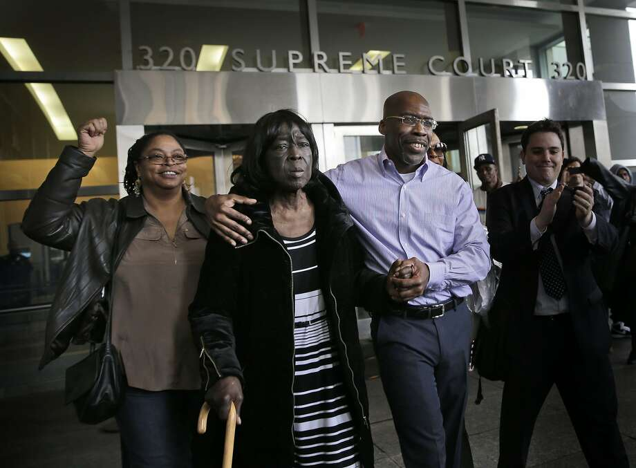 Jonathan Fleming (second from right) exits the courthouse with his arm around his mother, Patricia Fleming. Photo: Seth Wenig, Associated Press