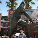 Father Mike Gavney with four year old son Conor from Pacifica, Ca sitting in front of the Willie Mays statue prior to entering the stadium for opening day between the Arizona Diamondbacks and San Francisco Giants at AT&T Park on April 8, 2014 in San Francisco, California. Conor is attending his first game since recovering from brain surgery after a serious car accident August 11, 2013.