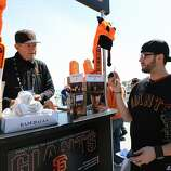 A Giant fan purchase a game program prior to entering the stadium for the Opening Day Game between the Arizona Diamondbacks and San Francisco Giants at AT&T Park on April 8, 2014 in San Francisco, California.