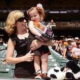 Mother Janie Scadina from San Jose, Califronia, holds her three-year-old daughter Emily, in the stands prior to the Opening Day Game between the Arizona Diamondbacks and San Francisco Giants at AT&T Park on April 8, 2014 in San Francisco, California.