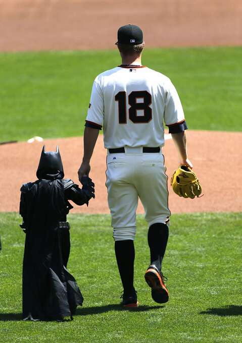 Giants pitcher Matt Cain leads Batkid, the superhero persona of young cancer survivor Miles Scott, onto the diamond at AT&T Park for the ceremonial first pitch on Opening Day. Photo: Michael Macor, The Chronicle