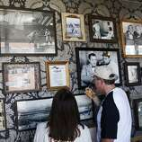 Mladen Vucicevic, right, and his friend Debbie Idiart look at photos alluding to the Giants' history on a wall in the Gotham Club on opening day, April 8, 2014 in San Francisco, Calif. In their home opener, a day game, the San Francisco Giants face the Arizona Diamondbacks. The Gotham Club is a multi-part social club at AT&T park that includes a bay cruise, an on-field bar before the game, and a speakeasy-style area within the park that includes a bowling alley and game room.