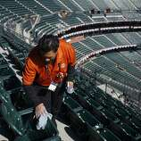 Tedocio Aguilera cleans seats in the view level on opening day at AT&T Park on April 8, 2014 in San Francisco, Calif. In their opening day game, the San Francisco Giants face the Arizona Diamondbacks.