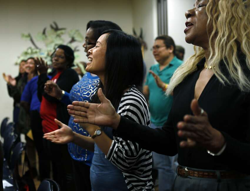 Participants chant and clap as a gathering of health, housing and poverty advocates concludes at a senior center in Oakland.