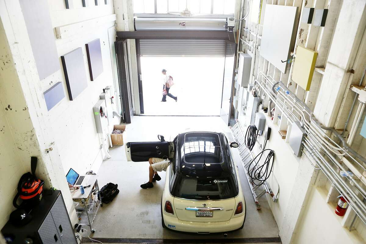 Patrick Handy installs the electronics needed to add the privately owned vehicle to the Getaround car sharing system at the company's headquarters on Tuesday, April 8, 2014 in San Francisco, Calif.