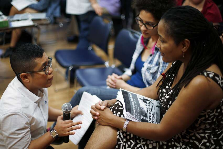 Dawn Phillips (left), co-director of programs at Causa Justa, speaks with City Councilwoman Lynette McElhaney (right) and Paige Kumm at a gathering of health, housing and poverty advocates at the Fruitvale- San Antonio Senior Center in Oakland.