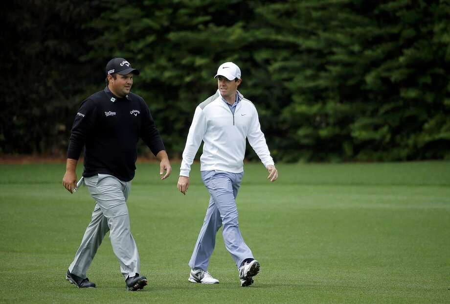 Patrick Reed (left) walks with Rory McIlroy during Tuesday's practice round. Photo: Mike Blake, Reuters