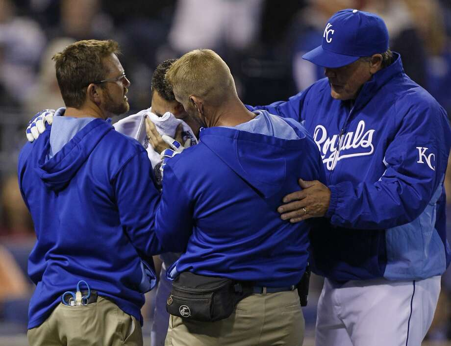 Infielder Omar Infante of the Royals is helped off the field by manager Ned Yost (right) and trainers after being hit by a pitch in the head on Monday night. Photo: Ed Zurga, Getty Images