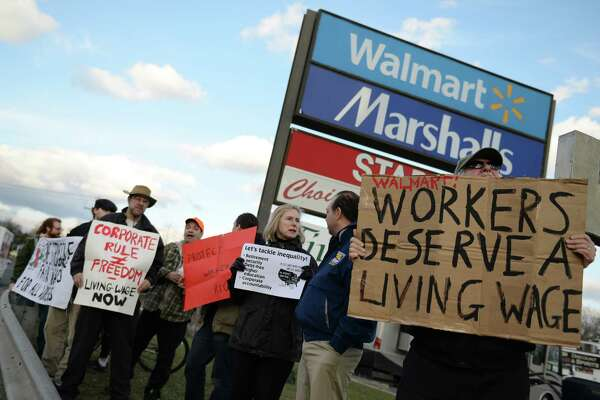 """Mike Toto, right, of Redding, holds up a sign along with others outside of Walmart in Danbury, Conn. Tuesday, April 8, 2014.  About a dozen people gathered for the Vigil for Inequality, suggesting that large corporations like Walmart pay their workers a living wage to """"create an economy that works for everyone, not just the rich.""""  24 vigils were held across the state in towns where poverty has increased, according to a report from Connecticut Voices for Children.  The vigils were organized the Connecticut Working Families Party, Connecticut Citizens Action Group, local chapters of MoveOn.org, and other groups and community organizations across the state."""