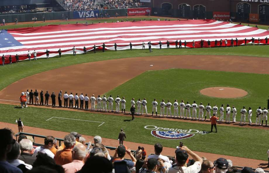 The National Anthem is sung during the opening ceremonies as the San Francisco Giants prepare to take on the Arizona Diamondback during their home opener at AT&T Park on Tuesday April 8, 2014, in San Francisco, Calif. Photo: Michael Macor, The Chronicle