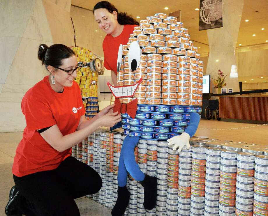 State Museum staff members Samantha Cassidy, left, and Nicole LaFountain make a last-minute adjustment to an exhibit for this year's Canstruction program, Storytown, at the New York State Museum Tuesday, April 8, 2014, in Albany, N.Y.  (John Carl D'Annibale / Times Union) Photo: John Carl D'Annibale / 00026403A