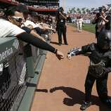Miles Scott, right, dressed as Batkid, is greeted by San Francisco Giants left fielder Michael Morse after throwing the ceremonial first pitch before the Giants' home-opener baseball game against the Arizona Diamondbacks in San Francisco, Tuesday, April 8, 2014. On Nov. 15, 2013, Miles a Northern California boy with leukemia, fought villains and rescued a damsel in distress whiled dressed as a caped crusader through The Greater Bay Area Make-A-Wish Foundation.