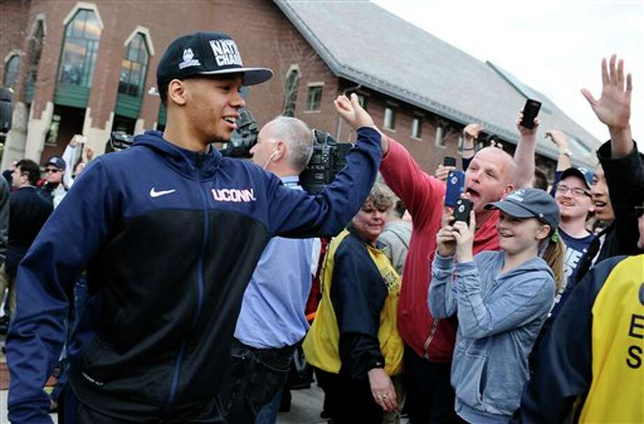 Connecticut's Shabazz Napier  slaps hands with fans as he arrives with his team to a pep rally  celebrating the program's fourth national championship, Tuesday, April  8, 2014, in Storrs, Conn. (AP Photo/Jessica Hill)