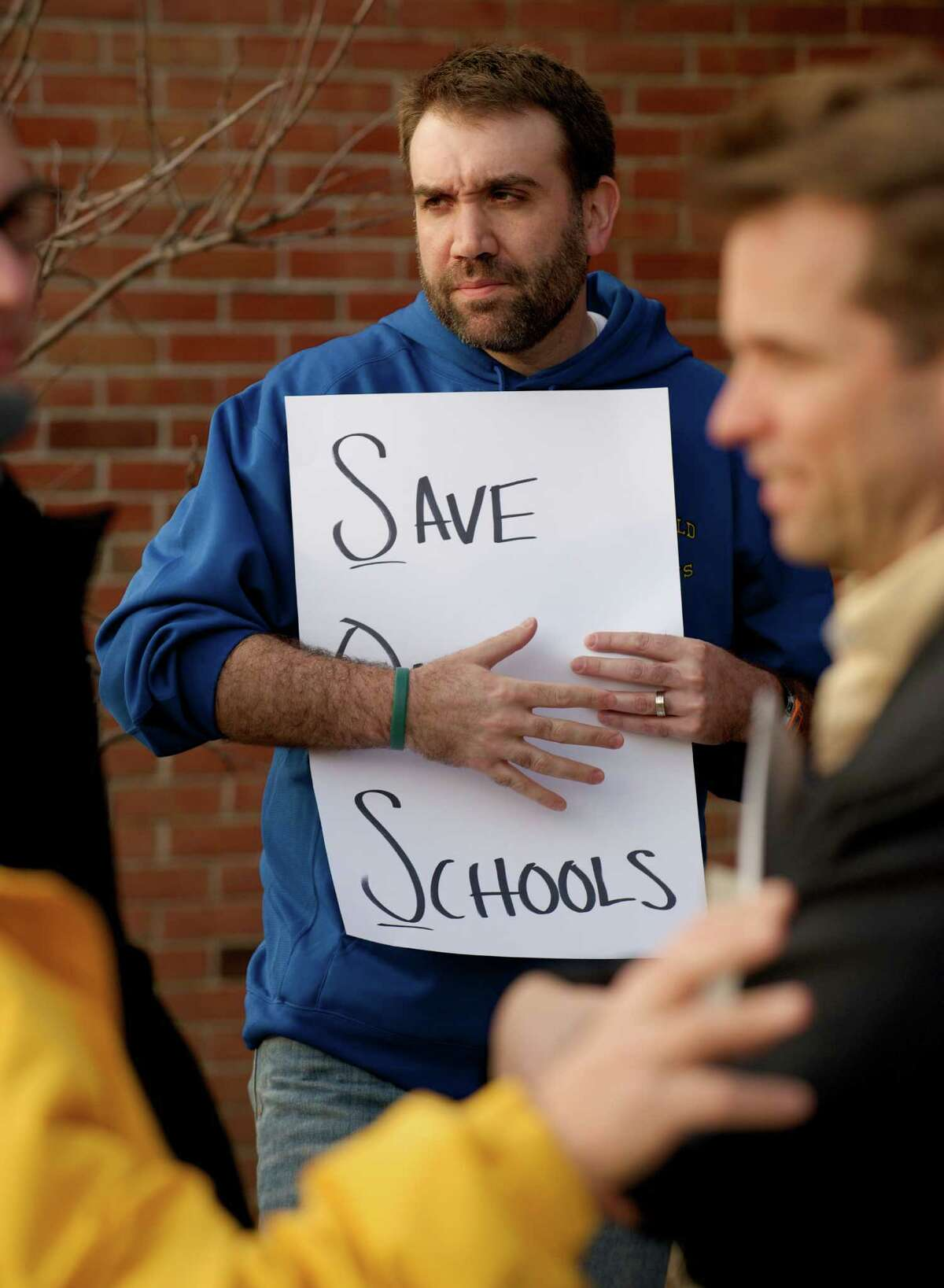 """Chris Buckley, 35, of Brookfield, holds a sign asking to """"Save Our Schools"""" during a parents and education staff rally to increase funding for the Brookfield, Conn school system, which was held before the Board of Finance public hearing, at Brookfield High School on Tuesday, April 8, 2014. Buckley has two children who will be students in the Brookfield School System."""
