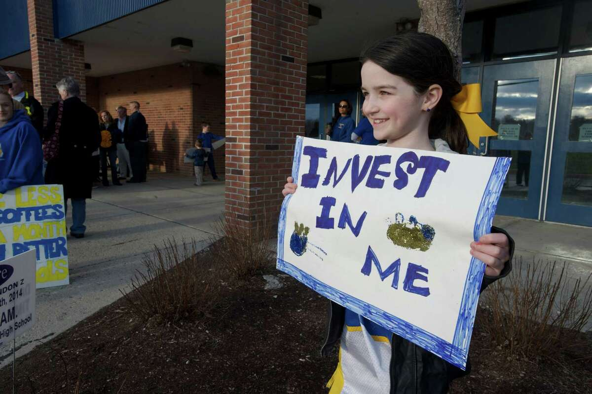 Kayla Zimmerman, 8, a Brookfield second grader holds up a sign during a parents and education staff rally to increase funding for the Brookfield, Conn school system before the Board of Finance public hearing at Brookfield High School on Tuesday, April 8, 2014.