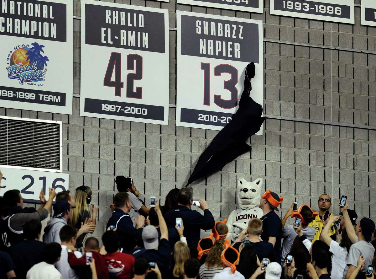 Carmen Velasquez, mother of Connecticut's Shabazz Napier, unveils her son's number on the Huskies Wall of Honor at a pep rally celebrating the the men's basketball team's NCAA championship, Tuesday, April 8, 2014, in Storrs, Conn.